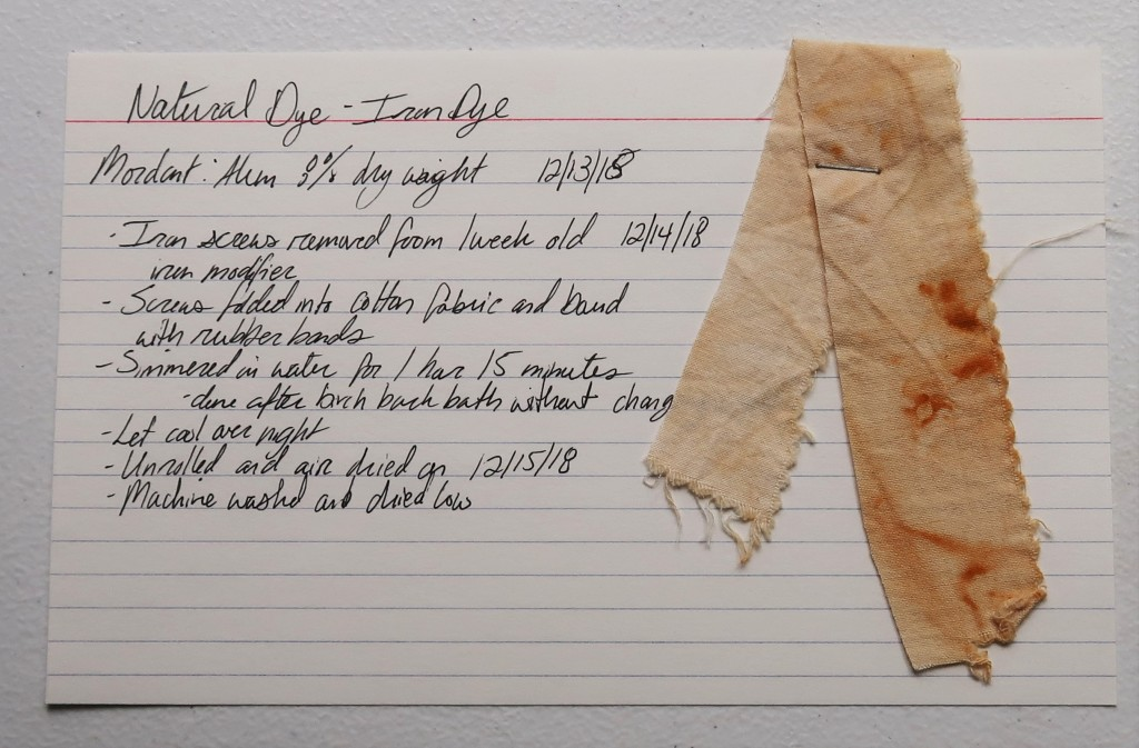 An index card laid flat on a white table. The left side of the card has hand written information that is written in text on this page for the iron dye. On the right is stapled a strip of cotton fabric that is a light orange/tan with splotches of rust.