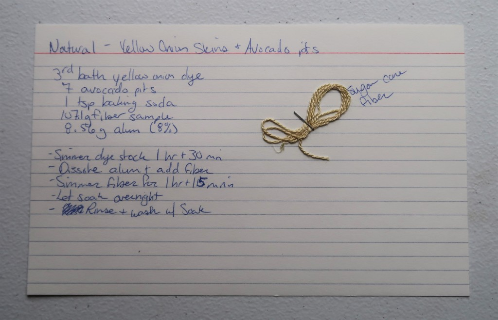 Index card on a white table. The information transcribed on the website page is hand written in blue ink. There is a sample of sugar cane fiber stapled to the index card. It is a light pinkish yellow.